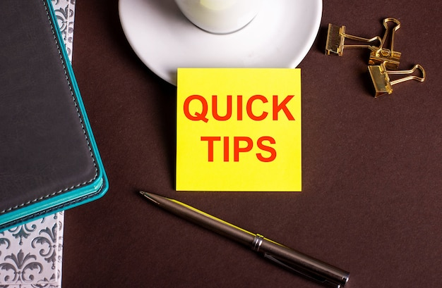 The words quick tips written on yellow paper on a brown background near a coffee cup and diaries