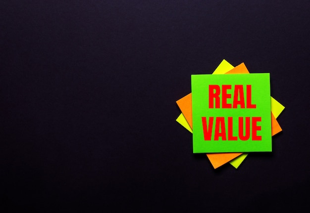The words real value on a bright sticker on a dark background. copy space
