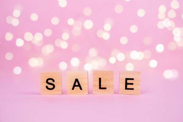 Words sale on a blurred pink background with beautiful bokeh garland lights