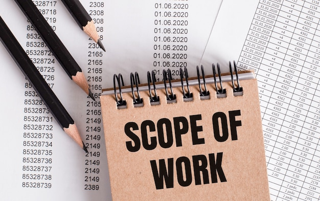The words scope of work is written on the brown notebook