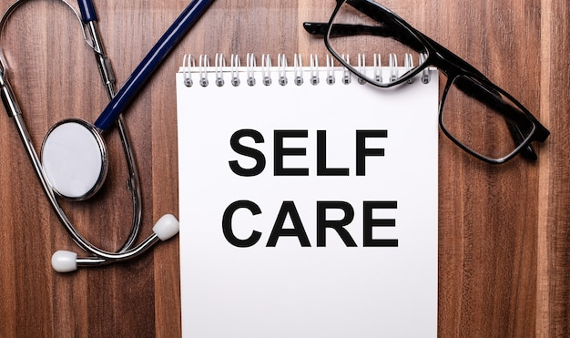 The words self care is written on white paper on a wooden background near a stethoscope and black-framed glasses. medical concept