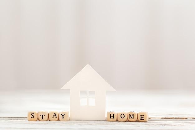 Слова остаются дома из деревянных блоков и белой бумаги дома, социального дистанцирования.
