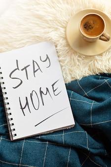 家にいる言葉はノート、コーヒーに書かれています。ウイルス発生の予防策としての自宅での自己検疫の概念。ホームオフィスのコンセプト。フラットレイ