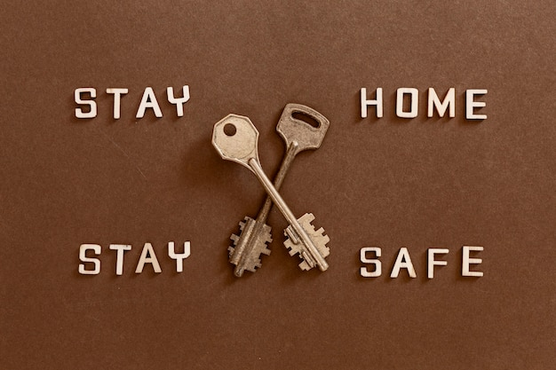 Words stay home stay safe made from wooden letters and two keys, concept of self quarantine at home as preventative measure against  corona virus covid 19 outbreak.