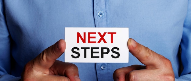 The words next steps is written on a white business card in a man's hands. business concept