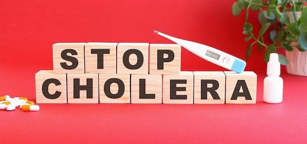 Stop choleraという言葉は、赤い背景に医薬品が入った木製の立方体でできています。