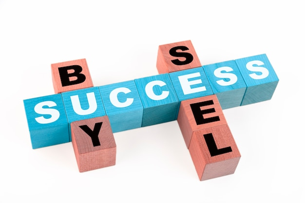 Words success, buy, seel collected in crossword with wooden cubes. copy space