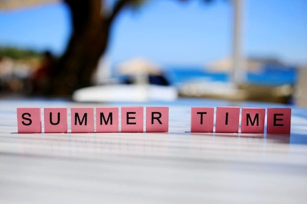 The words summer time written on pink wooden cubes with blurred tree and sea background