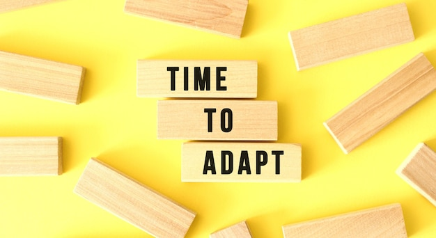 The words time to adapt are written on scattered wooden blocks on a yellow background.