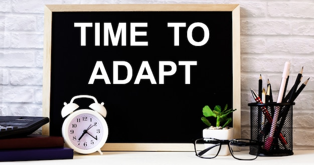The words time to adapt is written on the chalkboard next to the white alarm clock, glasses, potted plant, and pencils in a stand.