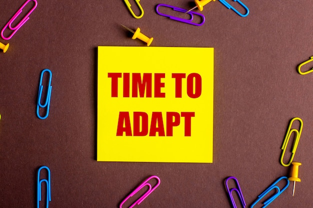 The words time to adapt is written in red on a yellow sticker on a brown background next to multi-colored paper clips.