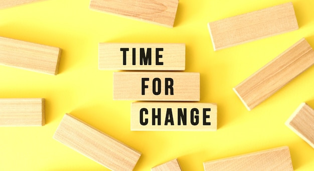 The words time for change are written on scattered wooden blocks on a yellow background