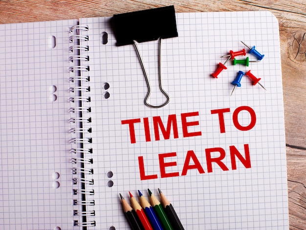 The words time to learn is written in a notebook near multi-colored pencils and buttons on a wooden background.