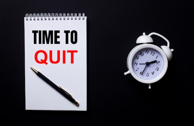 The words time to quit is written in a white notepad near a white alarm clock on a black background.