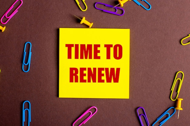 The words time to renew is written in red on a yellow sticker on a brown background next to multi-colored paper clips.