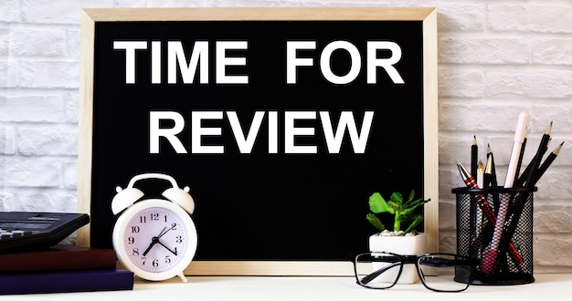 The words time for review is written on the chalkboard next to the white alarm clock, glasses, potted plant, and pencils in a stand