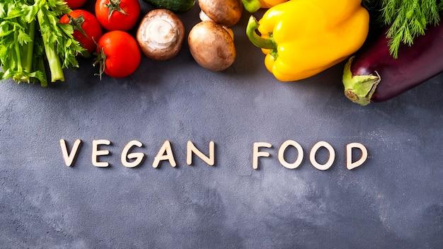 灰色の背景と生の有機野菜に木製の文字で書かれた「ビーガンフード」という言葉。健康的なビーガン食のための成分。上面図