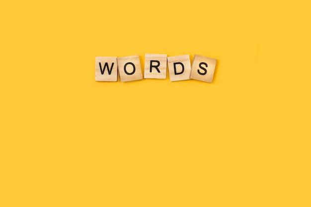 言葉は黄色の背景に木製の文字の立方体で書く