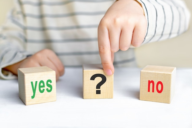 The words yes and no and a question mark on wooden cubes. the concept of choosing the right solution