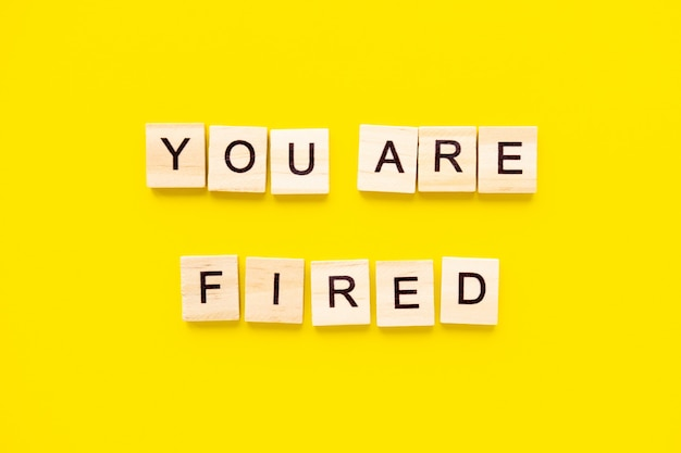 Words you are fired. wooden blocks with lettering on top of yellow table. human resource management and recruitment and hiring concept