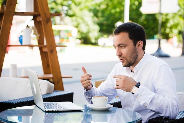 仕事とリラックス。オンライン会議。ノートパソコンでの作業のシャツに身を包んだ実業家屋外公園のカフェでスカイプで話しています。