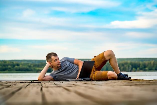 Работа и отдых. молодой человек, работающий на портативном компьютере, лежа на деревянном пирсе