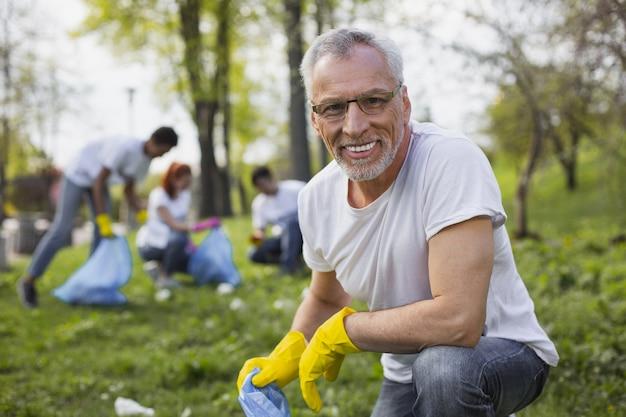 Работаю волонтером. опытный старший волонтер держит мешок для мусора и смотрит в камеру