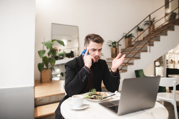 カフェで昼食。ビジネスの男性はコーヒーを飲み、サラダを食べる。