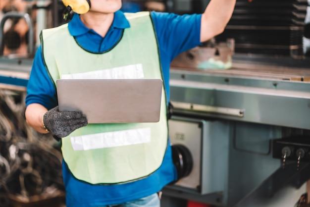 공장에서 일하십시오. 디지털 랩톱 컴퓨터를 사용하여 노란색 헬멧과 귀마개를 착용한 안전 작업복에서 일하는 아시아 노동자 남자 공장 작업장 산업 기계 전문가