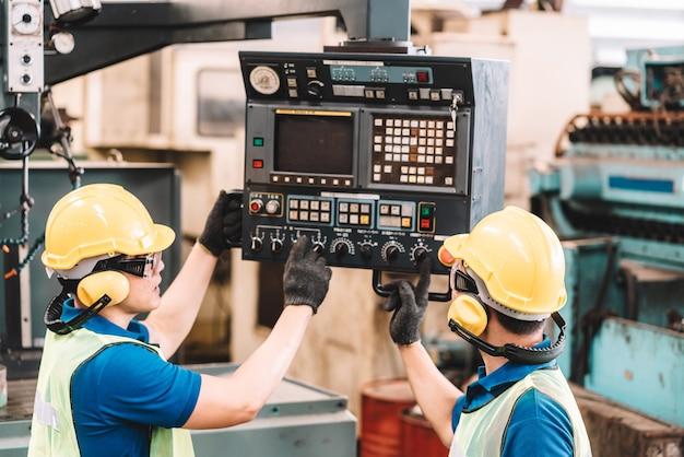 공장에서 일하십시오. 안전 작업에서 일하는 아시아 노동자 남자는 노란색 헬멧과 귀마개를 사용하여 장비를 사용합니다. 공장 작업장 산업 기계 전문가 프리미엄 사진
