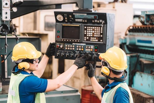 공장에서 일하십시오. 안전 작업에서 일하는 아시아 노동자 남자는 노란색 헬멧과 귀마개를 사용하여 장비를 사용합니다. 공장 작업장 산업 기계 전문가
