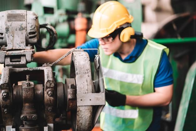 공장에서 일하십시오. 안전 작업복에서 일하는 아시아 노동자 남자 machine.in 공장 작업장 산업 회의 전문가를 사용하여 노란색 헬멧을 착용