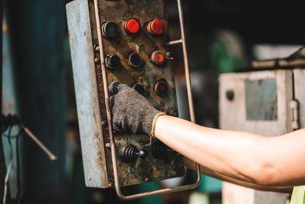 공장에서 일하세요. 장비를 사용하여 노란색 헬멧과 귀마개로 안전 작업복에서 일하는 아시아 노동자 남자의 손을 닫습니다. 공장 작업장 산업 기계 전문가
