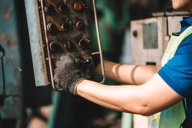 공장에서 일하세요. 장비를 사용하여 노란색 헬멧과 귀마개로 안전 작업복에서 일하는 아시아 노동자 남자의 손을 닫습니다. 공장 작업장 산업 기계 전문가 프리미엄 사진