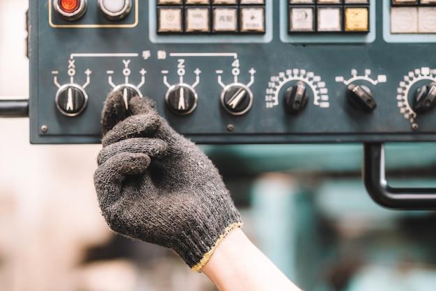 공장에서 일하세요. 제어 패널을 사용하여 노란색 헬멧과 장갑으로 안전 작업복에서 일하는 작업자 남자의 손을 닫습니다. 공장 작업장 산업 기계 전문가