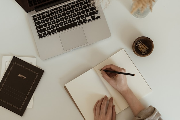 在宅勤務のコンセプト。美的ミニマリストワークスペースのフラットレイ。女性はノートにメモを書く