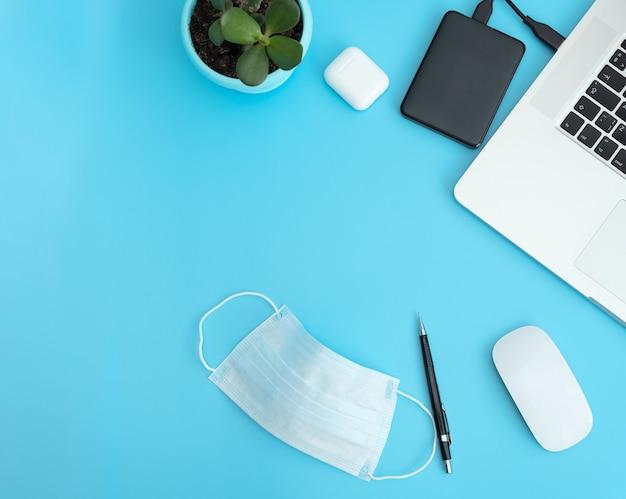 在宅勤務のコンセプト。ラップトップ、イヤホン、マウス、保護フェイスマスクを備えた職場の上面図。