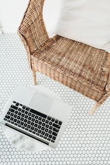 노트북, 베개가있는 등나무 의자 및 모자이크 바닥이있는 발코니에서 대리석 커피 테이블로 집에서 작업하십시오.