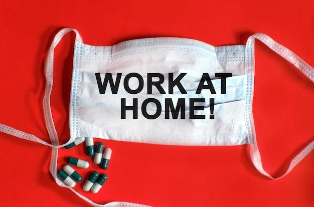在宅勤務-保護フェイスマスクのテキスト、赤い背景のタブレット