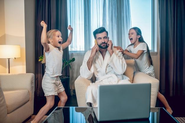 Работа на дому. две девушки развлекаются и мешают своему рабочему папе