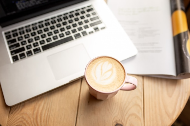 一杯のコーヒーで自宅で仕事をします。作業プロセスのある家庭環境。自分の時間。コーヒーを飲む時間。ノートパソコンでラテ。仕事で朝食します。コロナウイルスの最中にニュースを読む