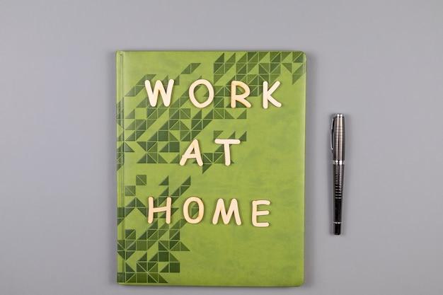 Работа дома слова, написанные деревянными буквами, блокнотом и ручкой на сером