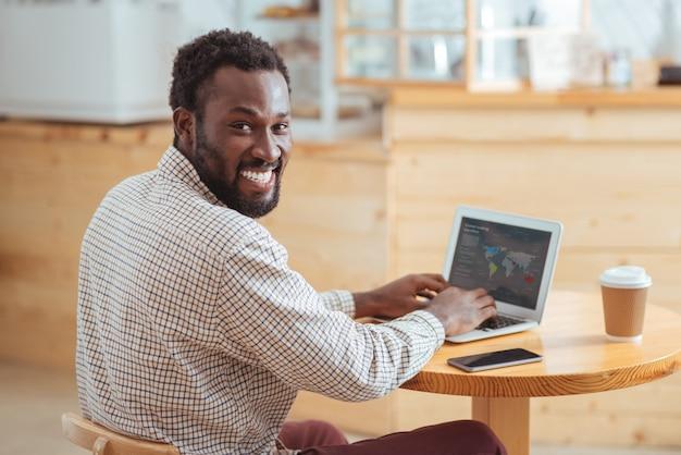 Работа приносит удовольствие. счастливый веселый человек сидит за столом в кафе и разрабатывает презентацию о глобальных торговых переводах на ноутбуке, улыбаясь в камеру