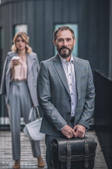 仕事、同僚。ブリーフケースと若い女性とビジネススーツで笑顔の大人のひげを生やした男性は通りのオフィスの近くの後ろでコーヒーを飲みます