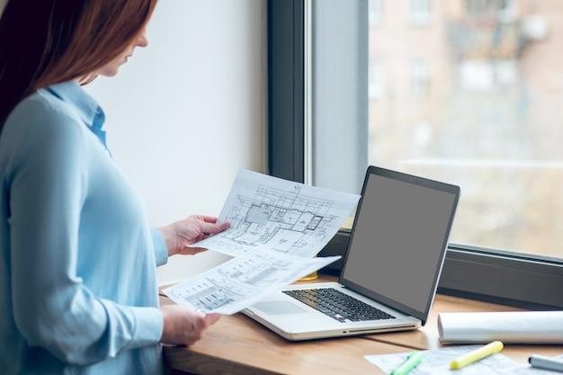 일, 집중. 밝은 블라우스를 입은 집중된 장발 여성은 낮 동안 실내 창문 근처에 서 있는 종이에 있는 건설 계획을 보고 있다