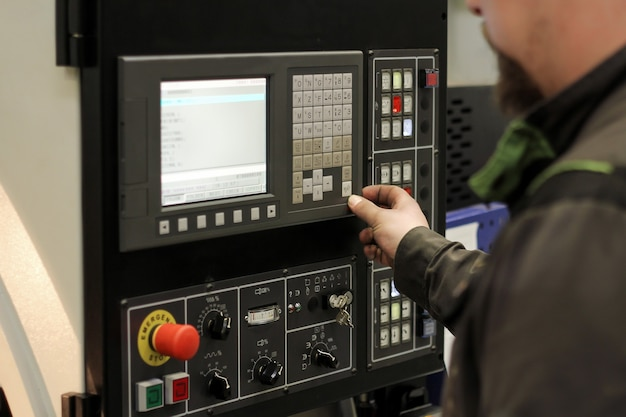 Work on the control panel of machine cnc. metalworking milling machine. cutting metal modern processing technology.