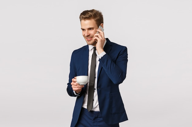 Work, corporate deals and business concept. charming, confident and elegant young bearded man in classic suit, holding smartphone near ear, calling wife from office, drink coffee from cup
