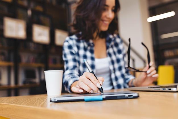 도서관에서 노트북으로 공부하는 젊은 갈색 머리 여자의 창조적 인 시간을 작동합니다. 현대 학생, 손에 초점, 검은 안경, 쾌활한 분위기, 웃고, 성공 놀고.