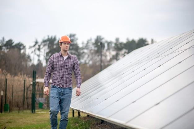 Рабочий день. сосредоточенный молодой взрослый человек в ярком шлеме гуляет возле инженерного сооружения на открытом воздухе во второй половине дня