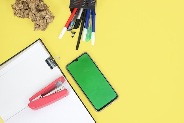 Work desk full of stationery isolated on yellow background